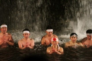 Purification ceremony during the waterfall cold of the boy firmness